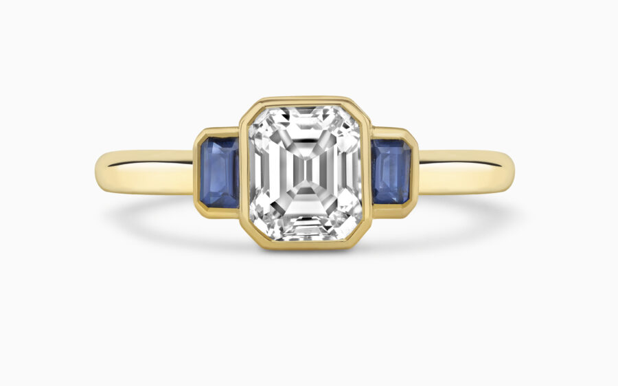 Emerald cut diamond with sapphire side stones - trilogy ring